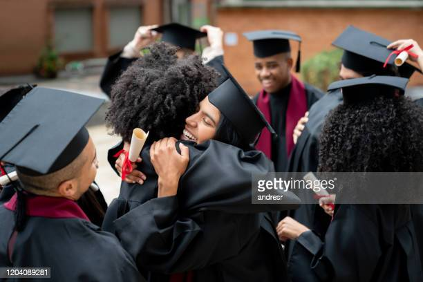 happy students hugging each other on their graduation day - alumni stock pictures, royalty-free photos & images