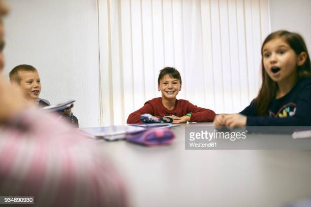 Happy students in class sitting at table