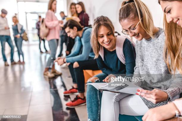 happy students learning from a textbook in a hallway. - high school student stock pictures, royalty-free photos & images