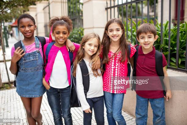 happy students standing arm around outside school - first day of school stock pictures, royalty-free photos & images