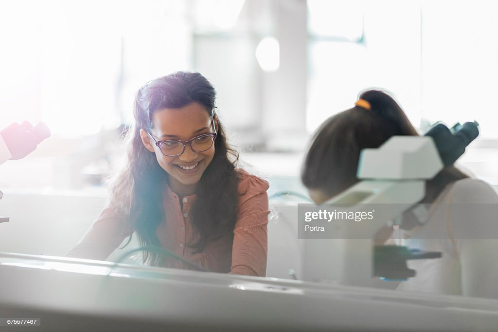 Happy students studying at desk in science class : Stock Photo