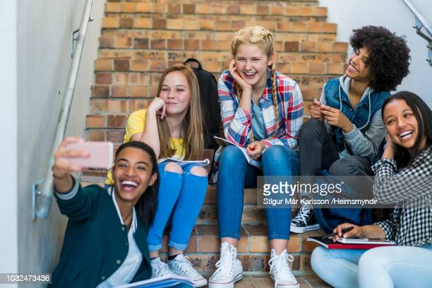 happy students taking selfie on steps in school - solo adolescenti foto e immagini stock