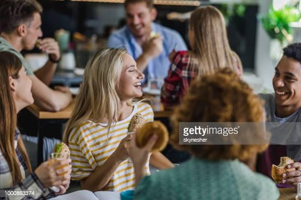 gelukkig studenten praten terwijl het hebben van lunch afbreken op cafetaria. - lunch stockfoto's en -beelden