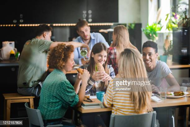 happy students talking while having lunch break at cafeteria. - canteen stock pictures, royalty-free photos & images