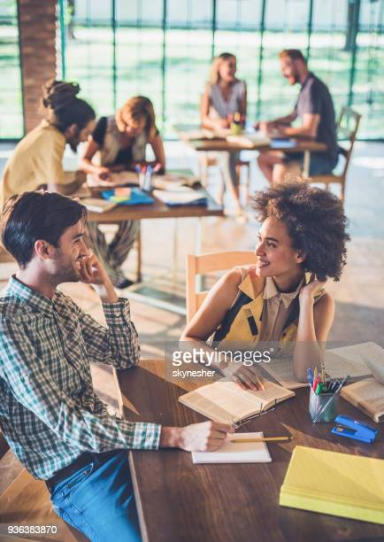 happy students talking while studying together in library. - incidental people stock pictures, royalty-free photos & images