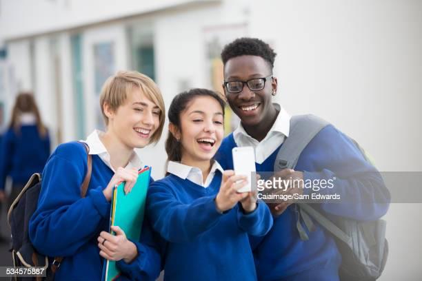 Happy students wearing school uniforms using smartphone in school corridor