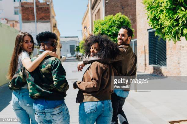 happy stylish friends walking on urban street - four people stock pictures, royalty-free photos & images