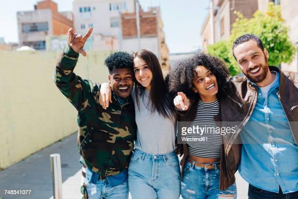 Happy stylish friends walking on urban street