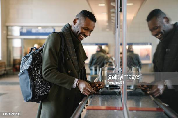 happy stylish man buying ticket in train station - credit card purchase stock pictures, royalty-free photos & images