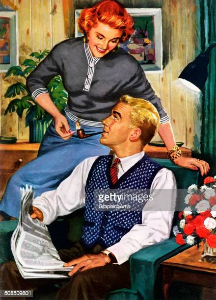 Happy suburban American housewife lighting her husband's tobacco pipe, as he reads the newspaper in the couples' den, 1953. Screen print.
