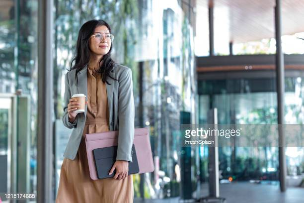 happy successful asian businesswoman holding a takeaway coffee cup and files on the street next to a glass building - blue dress stock pictures, royalty-free photos & images