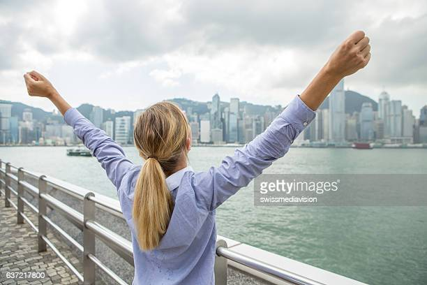 Happy successful business woman celebrating arms outstretched Hong Kong