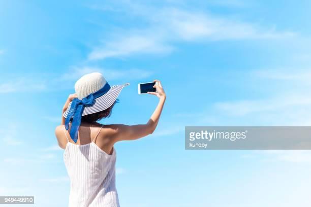 happy summer trip on the beach. woman selfie portrait with blue sky. - 写真を撮る ストックフォトと画像
