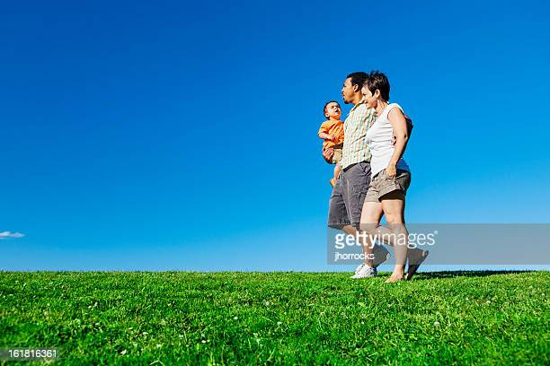 happy summertime family walking in park - white wife black baby stock photos and pictures