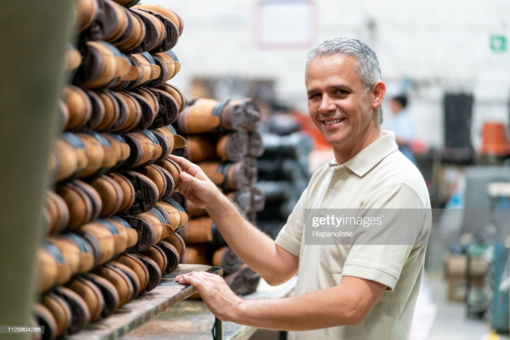 Happy supervisor at a shoe factory standing next to a stack of boots smiling at camera : Stock Photo