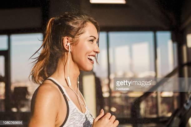 happy sweaty woman running on treadmill in a gym - ginásio imagens e fotografias de stock