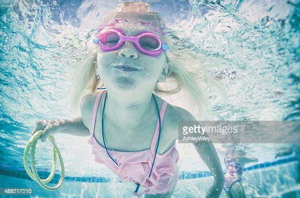 Happy swimming little girl underwater wearing goggles