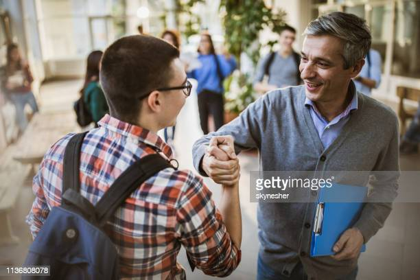 happy teacher and high school student greeting in a hallway. - instructor stock pictures, royalty-free photos & images