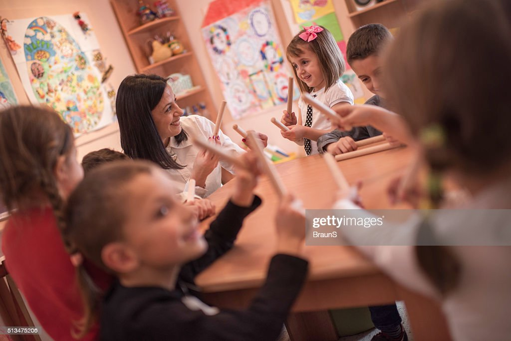 Happy Teacher And Kids During A Music Class In Preschool Stock Photo