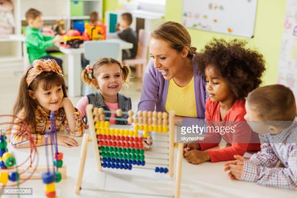 happy teacher and kids learning to count on abacus at preschool. - nursery school child stock pictures, royalty-free photos & images