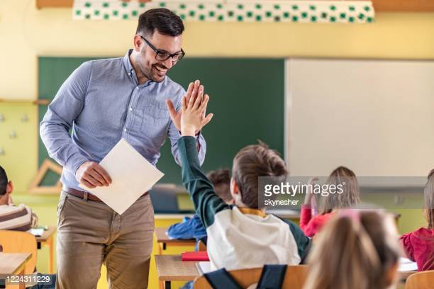 happy teacher and schoolboy giving each other high-five on a class. - schoolboy stock pictures, royalty-free photos & images