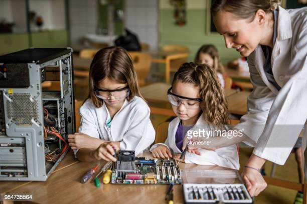 happy teacher assisting school girls in repairing computer component in the classroom. - stem stock photos and pictures