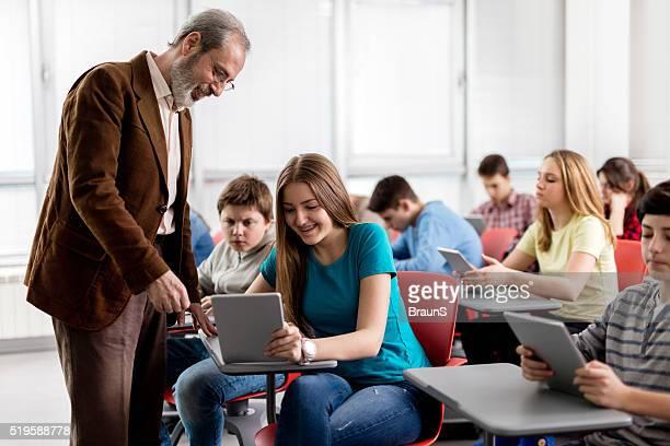 Profesor ayudando un adolescente Feliz estudiante en una moderna con montaje tipo aula.