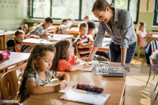 insegnante felice che comunica con il suo studente durante una lezione alle elementari. - maestra foto e immagini stock