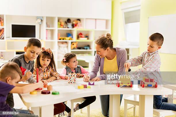 happy teacher enjoying with group of children at preschool. - preschool building stock pictures, royalty-free photos & images