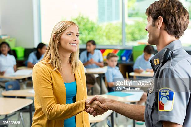 Happy teacher greets police officer in classroom