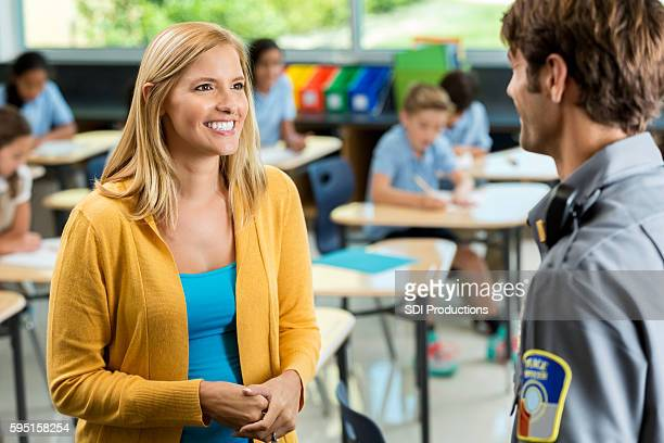 Happy teacher in school classroom having discussion with security officer