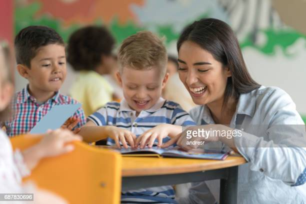 happy teacher reading a book with a student at the school - kids reading in classroom stock pictures, royalty-free photos & images