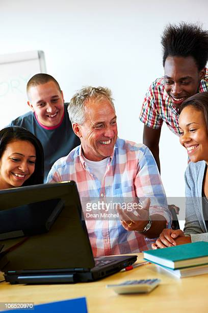 happy teacher showing students something on laptop - incidental people stock pictures, royalty-free photos & images