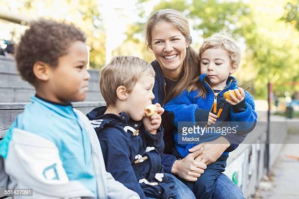 Happy teacher sitting with children outside kindergarten