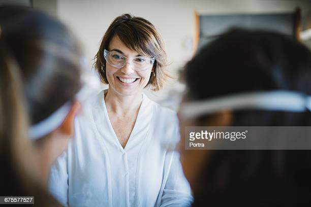 Happy teacher wearing protective glasses in class