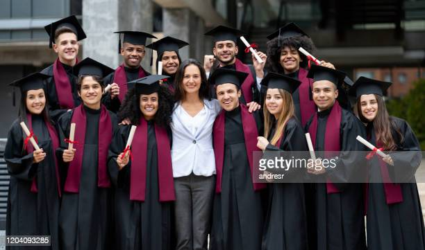 happy teacher with a group of graduating students - alumni stock pictures, royalty-free photos & images