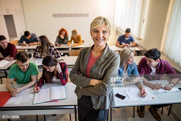 Happy teacher with arms crossed standing in the classroom.