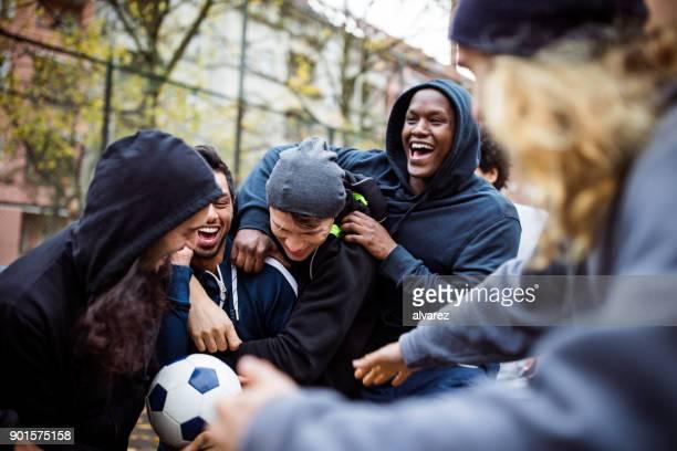 glückliches team genießen beim fußballspielen in stadt - spiel sport stock-fotos und bilder