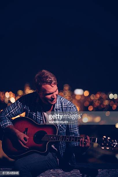 Happy teen guitarist playing outside on a rooftop