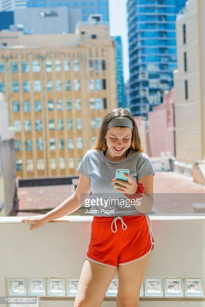 happy teen on smartphone - shorts stock pictures, royalty-free photos & images