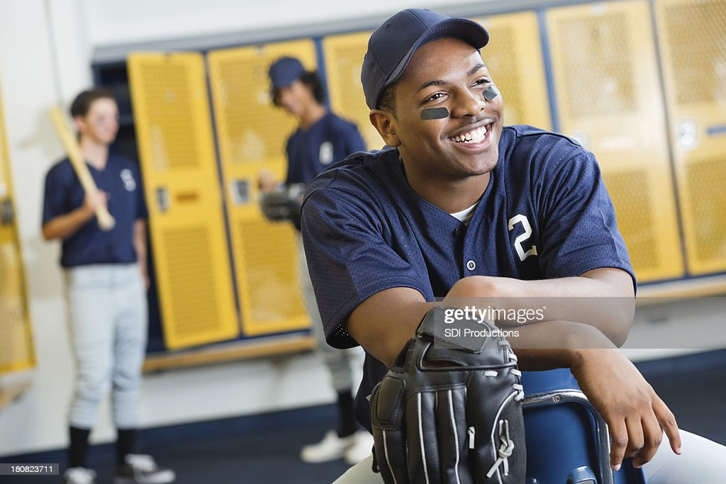 Happy Teenage Baseball Player In High School Locker Room Stock Photo