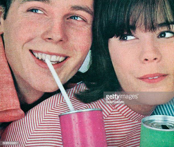 A happy teenage boy and girl sipping through straws from aluminum soda cans cearly 1960s Screen print