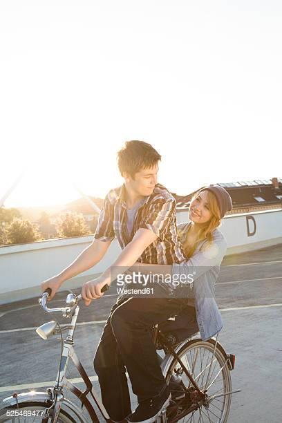 Happy teenage couple outdoors on bicycle
