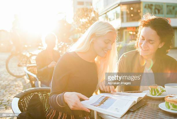 Happy teenage friends studying on table at sidewalk cafe
