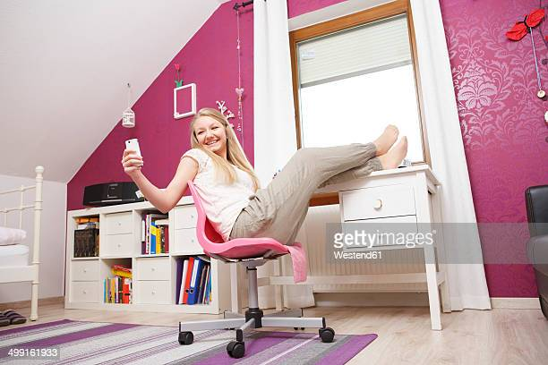 Happy teenage girl at her room using smartphone