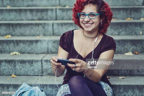 adolescente feliz navegando no telefone e olhando para a câmera - cabelo pintado de vermelho - fotografias e filmes do acervo