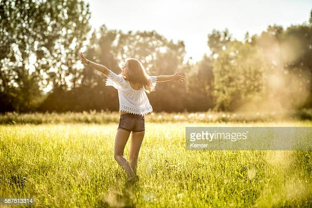 happy teenage girl dancing in meadow - hot pants stock photos and pictures