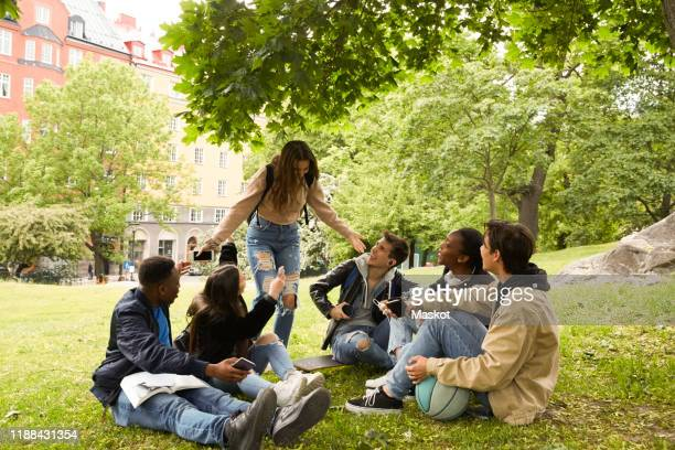 happy teenage girl gesturing while standing by friends sitting on land at park - public park stock-fotos und bilder