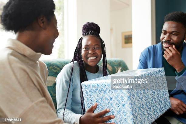 happy teenage girl holding christmas gift at home - 誕生日の贈り物 ストックフォトと画像
