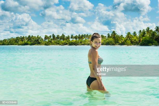 Happy teenage girl standing in front of an Caribbean island